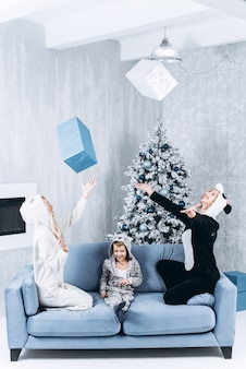 Los niños arrojan las cajas de regalo en el fondo del árbol de navidad decorado