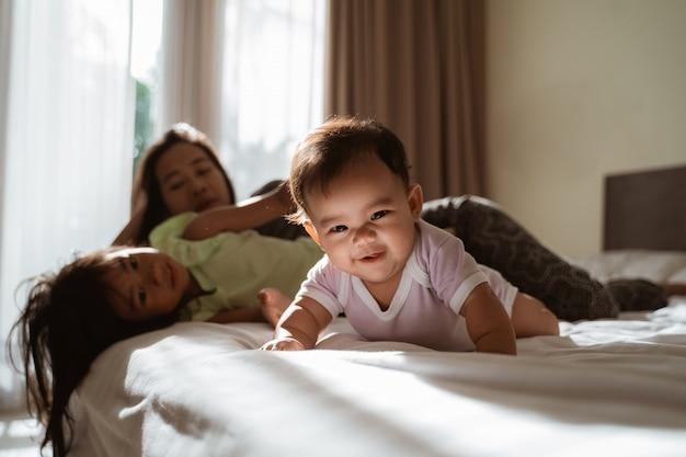 Niños asiáticos acostados en la cama con su madre junto a ellos