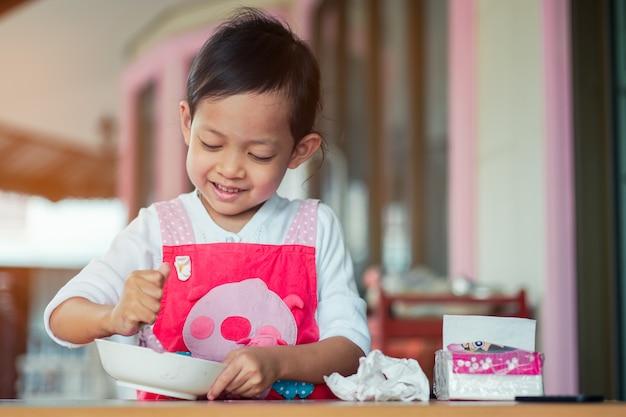 Niños asiáticos cocinando y sonriendo con felicidad en casa