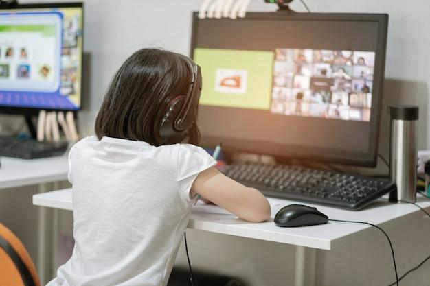 Los niños asiáticos están aprendiendo computadora en línea, escuela en casa