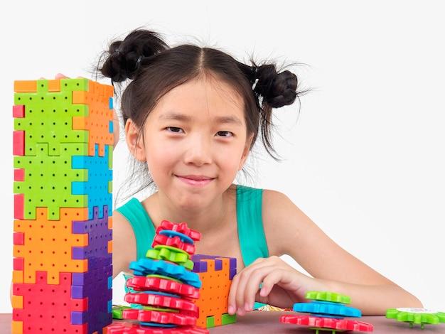 Niños asiáticos están jugando rompecabezas creativo juego de bloques de plástico