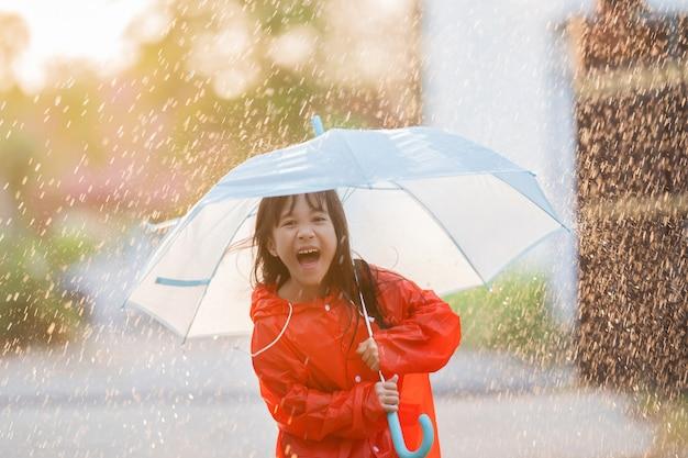 Niños asiáticos extendiendo paraguas jugando bajo la lluvia, ella lleva ropa impermeable.