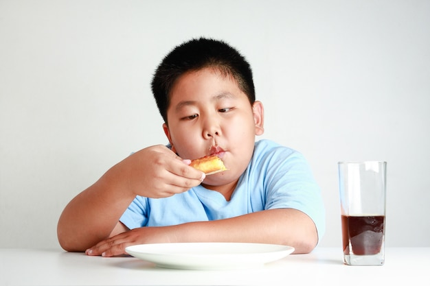 Los niños asiáticos gordos comen pizza en una mesa blanca con néctar de soda.