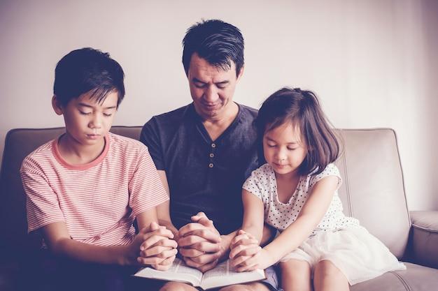 Niños asiáticos multiculturales rezando con su padre en casa, familia rezando