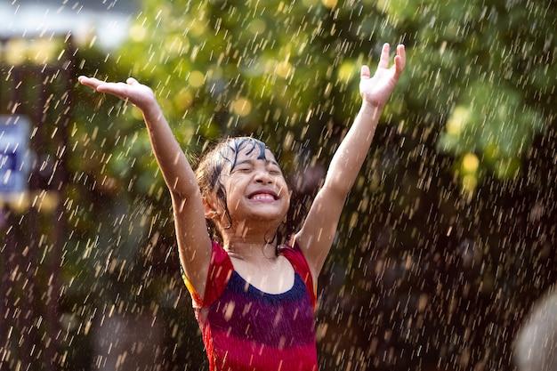 Los niños asiáticos que juegan bajo la lluvia son felices.