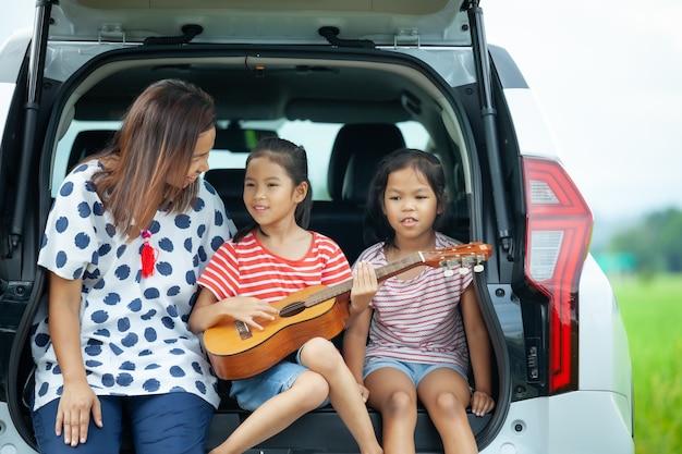 Los niños asiáticos y su madre tocando la guitarra y cantando una canción juntos en el maletero de un automóvil