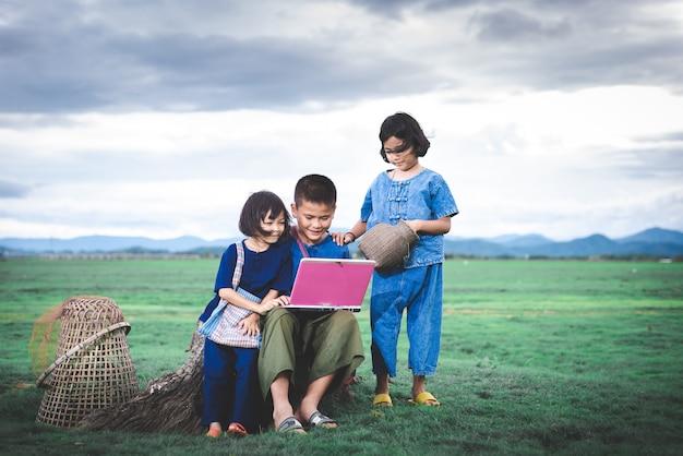 Niños asiáticos con vestimenta local están usando una computadora portátil para educación y comunicación en el campo de tailandia