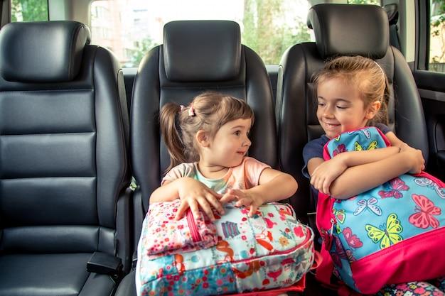 Los niños en el auto van a la escuela, felices y dulces rostros de hermanas