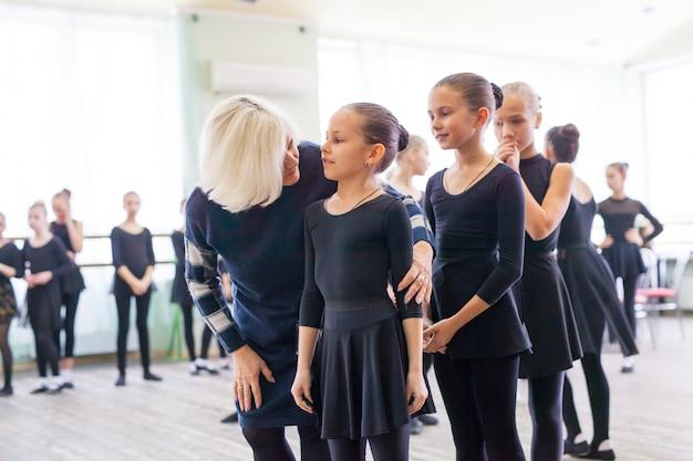Los niños bailan con un entrenador en una gran sala de entrenamiento.