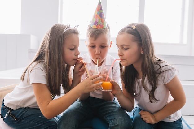 Niños bebiendo de vasos en la fiesta de cumpleaños