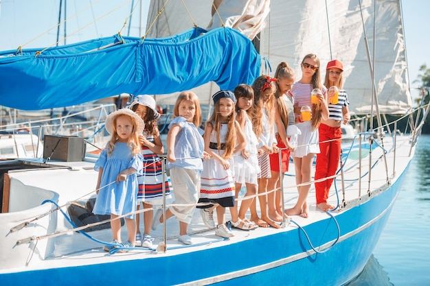 Los niños a bordo del yate bebiendo jugo de naranja. las niñas adolescentes o niños contra el cielo azul al aire libre. ropa de colores. moda infantil, verano soleado, conceptos de río y vacaciones.