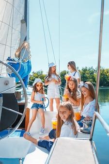 Los niños a bordo del yate de mar bebiendo jugo de naranja.