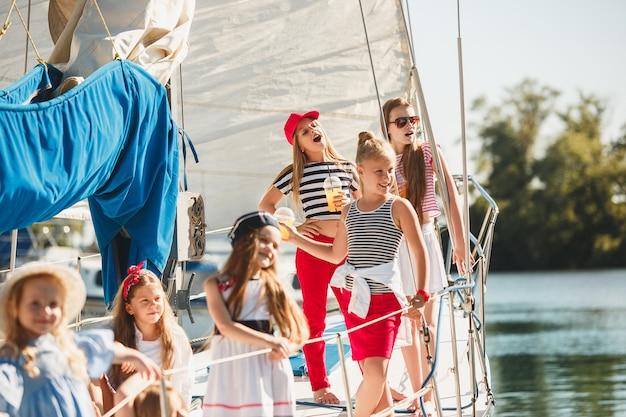 Niños a bordo del yate de mar bebiendo jugo de naranja.
