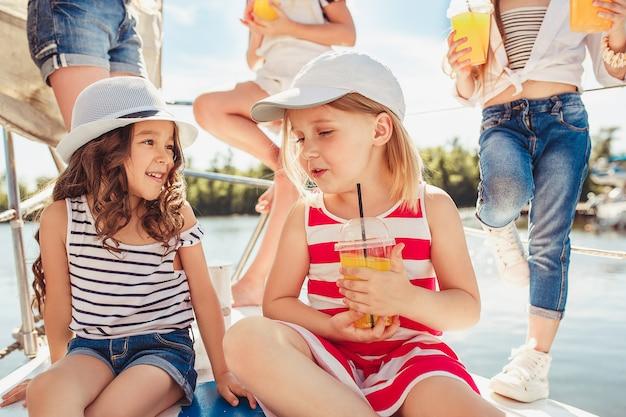 Niños a bordo del yate de mar bebiendo jugo de naranja