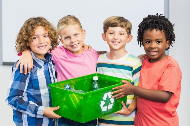 Niños con botella reciclada en caja