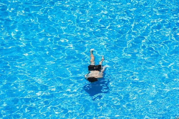 Niños buceando en una piscina en verano