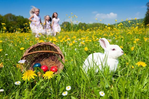 Niños en búsqueda de huevos de pascua con conejito