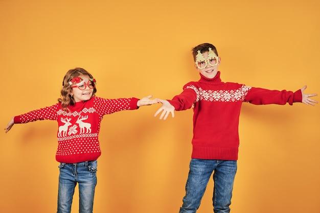 Niños en cálidos suéteres navideños rojos