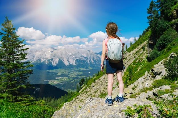 Niños caminando en un hermoso día de verano en las montañas de los alpes de austria, descansando sobre una roca y admirando la increíble vista a los picos de las montañas. ocio activo de vacaciones familiares con niños. diversión al aire libre y actividad saludable