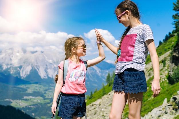 Niños caminando en un hermoso día de verano en las montañas de los alpes de austria, descansando sobre una roca y admirando la increíble vista a los picos de las montañas. ocio activo de vacaciones familiares con niños. diversión al aire libre y actividad saludable.