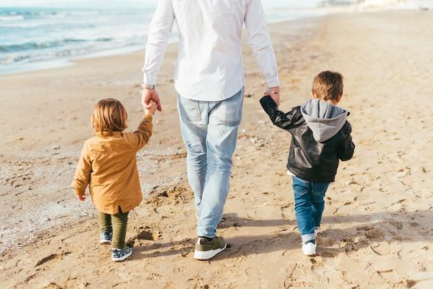 Niños caminando en la playa con papá.