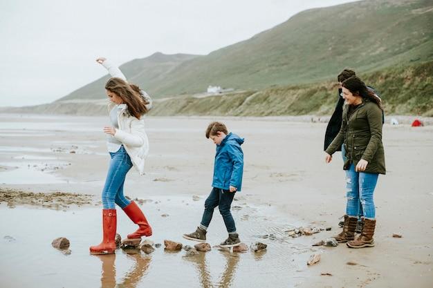 Niños caminando sobre piedras en la playa