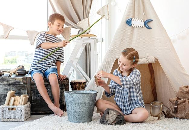 Los niños capturando peces de madera con caña casera en la habitación de luz