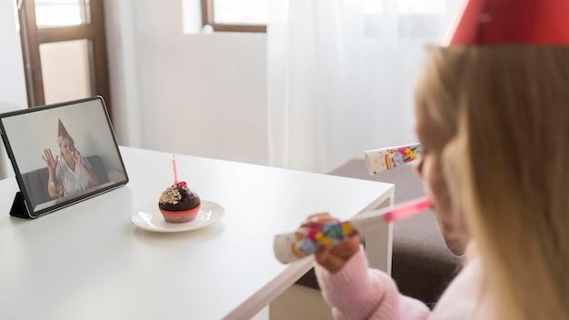 Niños en casa en cuarentena celebrando cumpleaños sobre tableta