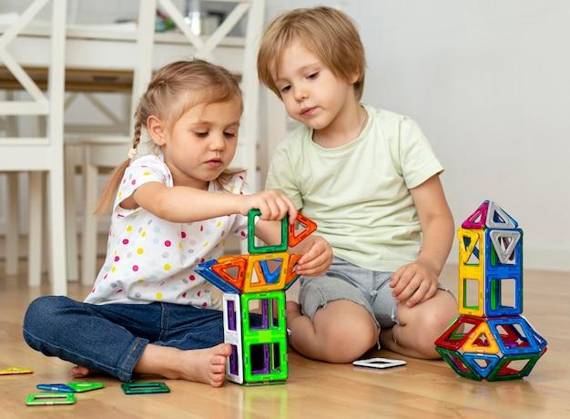 Niños en casa jugando con juguetes