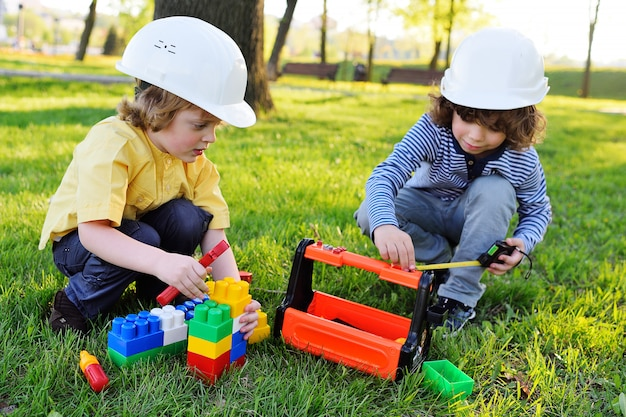 Los niños en cascos blancos de construcción juegan en trabajadores con herramientas de juguete.