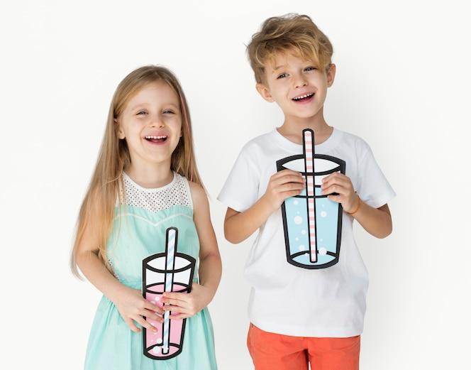 Niños caucásicos que sostienen beber papel