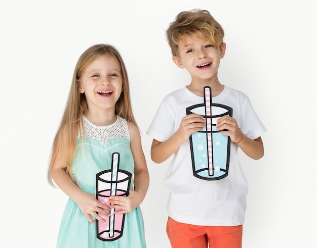 Niños caucásicos sosteniendo papel bebiendo