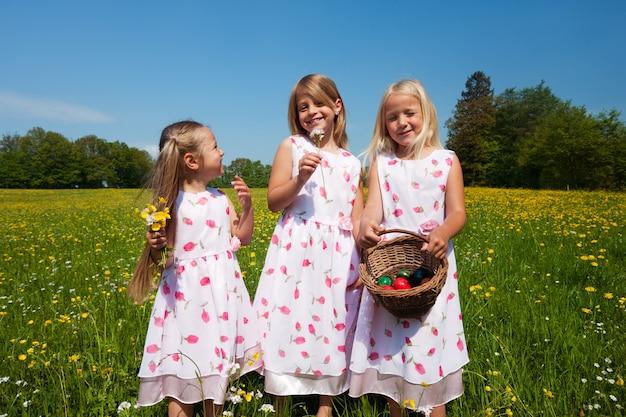 Niños a la caza de huevos de pascua con cestas.