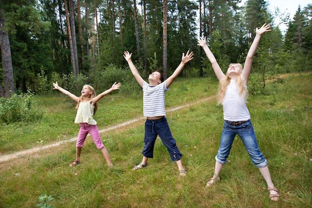 Los niños en el césped del bosque y disfrutan la vida en los deportes.