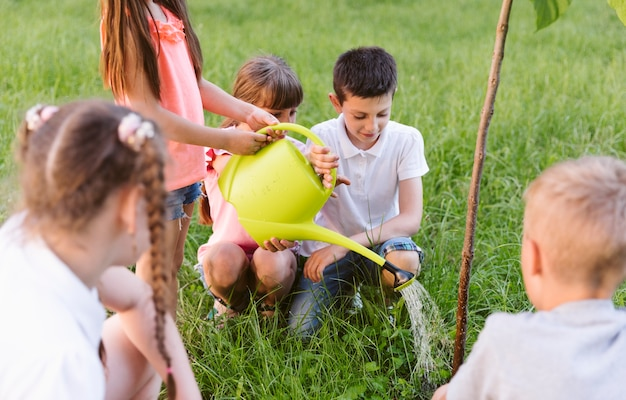 Niños chapando y regando árboles