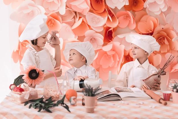 Niños en chefs uniformes de pie cerca de la mesa de la cocina.