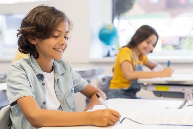 Niños en clase escribiendo