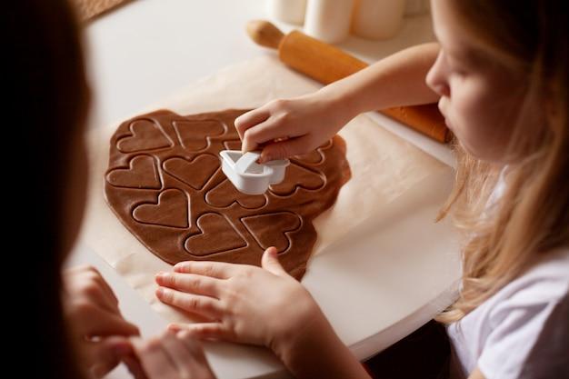 Los niños en la cocina hacen galletas caseras cortadas de masa en forma de corazón