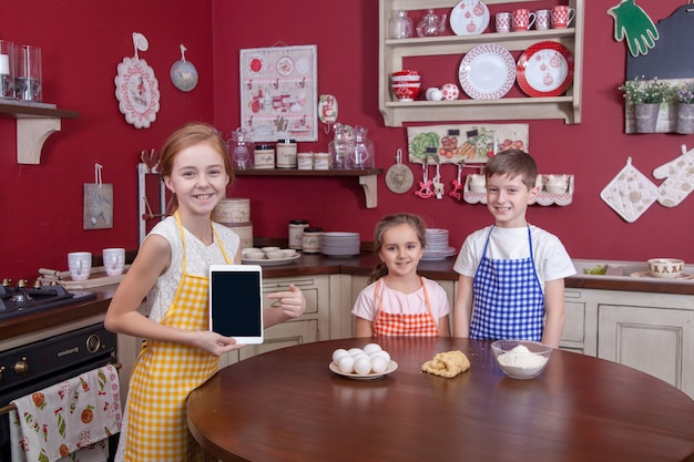 Niños en la cocina tratando de aprender a cocinar. mejores amigos en delantales sosteniendo pasteles en sus manos y haciendo pasteles en la cocina y mirándose. tiro del estudio.