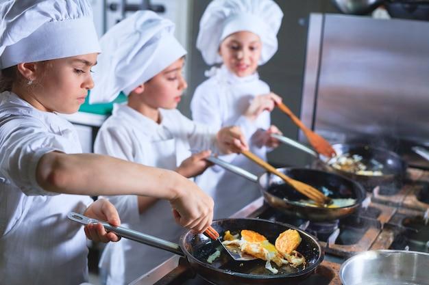 Niños cocinando el almuerzo en la cocina de un restaurante.