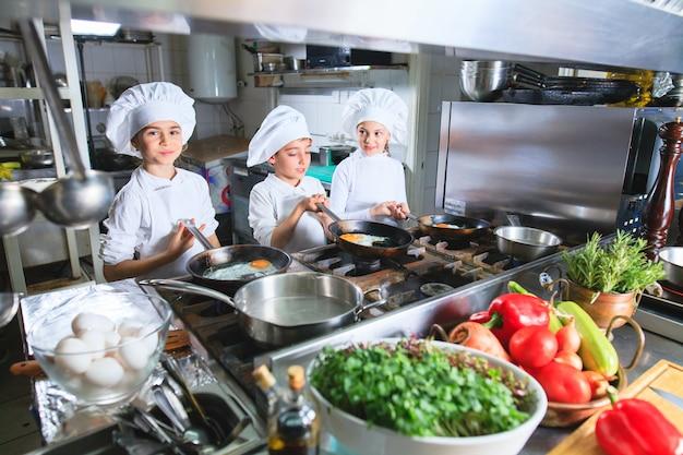 Niños cocinando el almuerzo en un restaurante de cocina.
