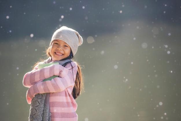 Niños colegiala abrazando libro y sonriendo al aire libre