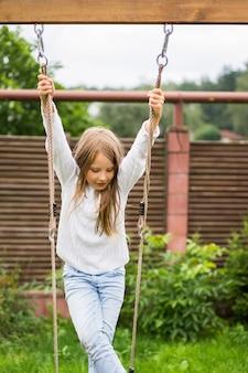 Niños en el columpio. niña columpiándose en un columpio en el patio. verano divertido.