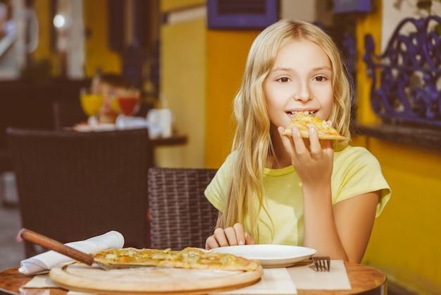 Los niños comen pizza y beben jugo al aire libre.