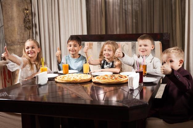 Los niños comen pizza en un restaurante.