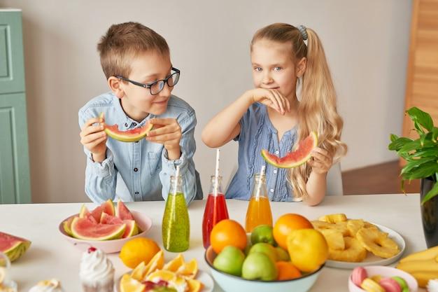 Los niños comen rodajas de sandía en la cocina