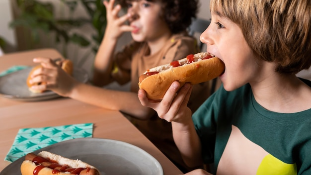 Niños comiendo hot dogs juntos
