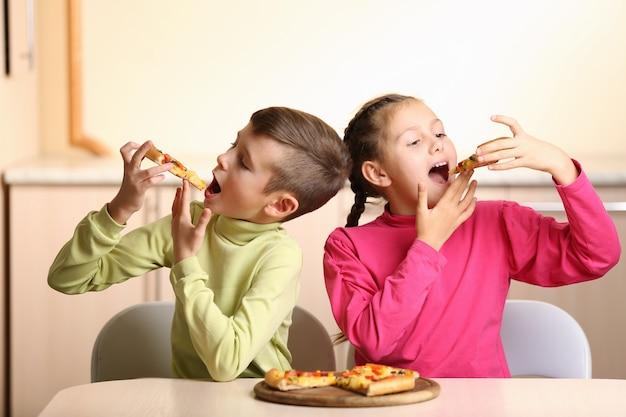 Niños comiendo pizza en casa.