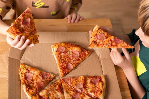 Niños comiendo pizzas juntos