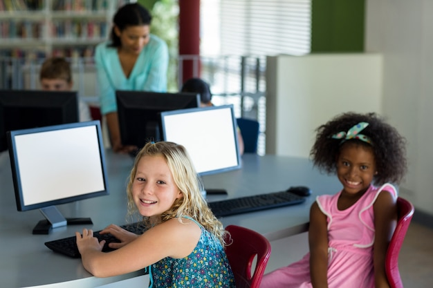 Niños con computadoras contra maestra